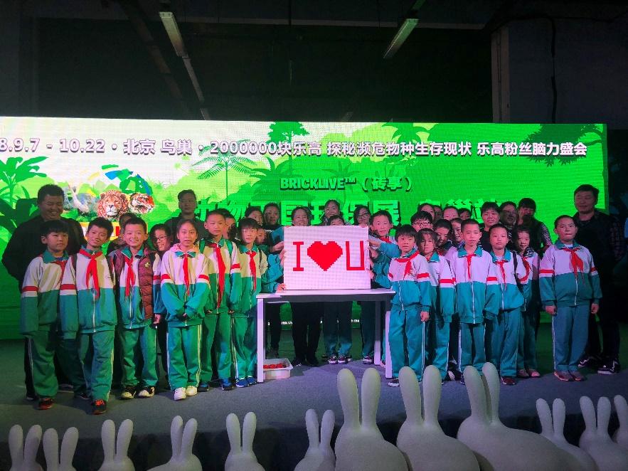 """10月21日,中国创投公益联盟与BRICKLIVE(砖享)动物王国环保展联合发起的""""关爱动物,一路童行""""公益行活动在国家体育场(鸟巢)举办。  学生聆听乐高老师的讲解  学生拼搭互动体验 此次公益活动以""""守护你的世界""""为主旨,一群来自打工子弟学校的学生及家长参加。孩子们在""""海洋""""、""""冰雪""""、""""荒野""""、""""丛林""""四大地带参观展品,观看1:1比例的动物模型,了解这些濒"""